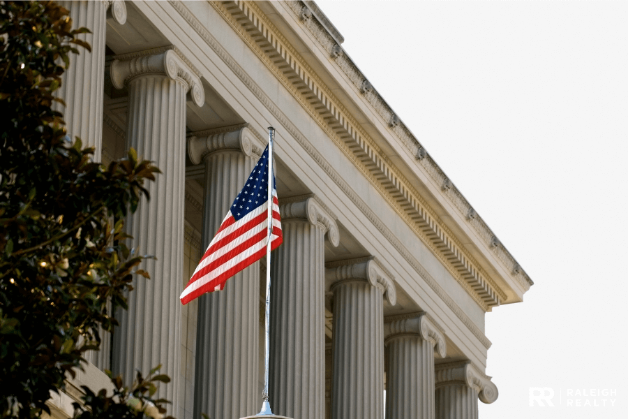 United States Flag in the foreground with a government building in the background